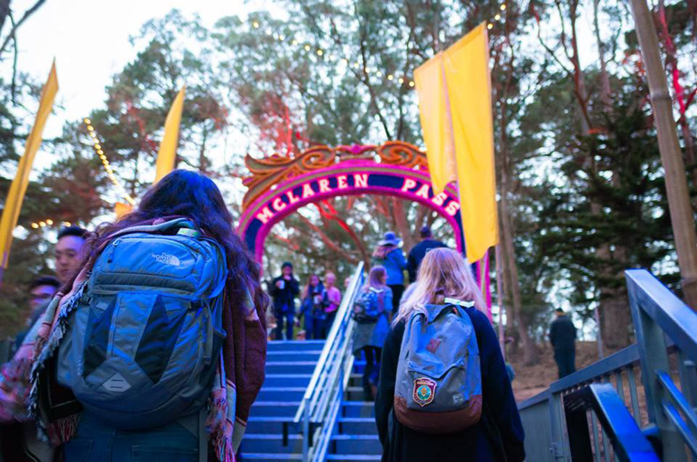 Image of two women wearing backpacks climbing stairs at a festival